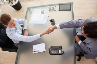 Above view of young consultant shaking hands with customer.jpeg