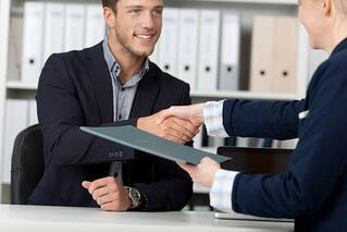 Happy businessman shaking hands with a female interviewer in office.jpeg